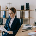 female lawyer in suit with documents in hands at workplace in office